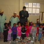 Maria & Jennifer from the Emmanuel kitchen staff, Roger from Woolworths, and some of the Grade 0 childrden with tins donated by Woolworths Steenberg Village.