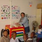 Teacher Cher distributing party packs to Pre-Grade R learners