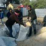 Joseph Mphala helps Sylvia Khalipa Dimala to some sand for her shack which was flooded
